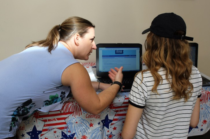 Director of Campus Life Allyson Gleason shows DCCC student Shelby McAlister how to register to vote online. Photo by Brian Devine